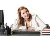 Beautiful girl smiling while sitting at a desk in an office — Stock Photo