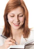 Meisje met gouden haren maakt notities op een pad — Stockfoto