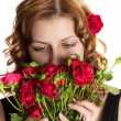 Girl smelling roses on a white background isolated — Stock Photo