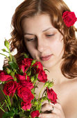Pretty green-eyed girl with a bouquet of red roses — Stock Photo