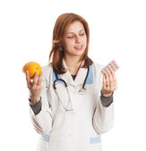 Female doctor offers an orange — Stock Photo