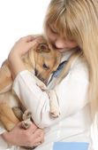 Kind woman veterinarian, hugging a puppy — Stock Photo