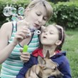 Mother and daughter blow soap bubbles — Stock Video