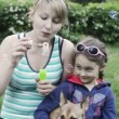 Mother and daughter blow soap bubbles — Stock Video #26384921