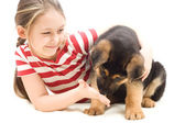 Puppy sniffs the hand of a little girl — Stock Photo