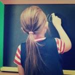 Schoolgirl writes on blackboard — Stock Photo #44499825