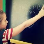 Schoolgirl writes on blackboard — Stock Photo #44499869