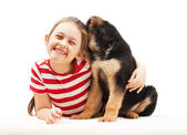 Cheerful little girl hugging a puppy — Stock Photo