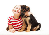 Cheerful child tenderly hugging a puppy — Stock Photo