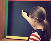 Schoolgirl and blackboard — Stock Photo
