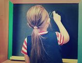 Schoolgirl writes on blackboard — Stock fotografie