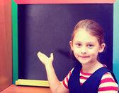 Schoolgirl writes on blackboard — Stok fotoğraf