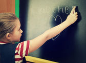Schoolgirl writes on blackboard — Stock Photo