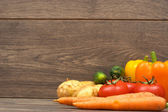 Peppers, carrots, potatoes, cucumbers and tomatoes on a wooden b — Stock Photo