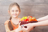 Little girl takes hands basket with vegetables — Stock Photo