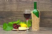 Vinho, queijo e frutas em um fundo de madeira — Fotografia Stock