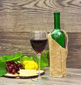 Vino e frutti su fondo in legno — Foto Stock