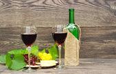 Due bicchieri di vino rosso e frutta su fondo in legno — Foto Stock