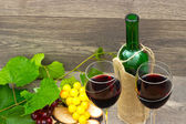 Two glasses of red wine and grapes — Stock Photo