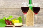 Vino rosso e frutta su fondo in legno — Foto Stock