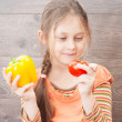 Beautiful little girl holds fresh vegetables — Stock Photo #48150789