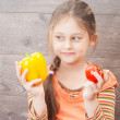 Beautiful little girl holds fresh vegetables on a wooden backgro — Stock Photo #48150875