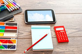 Set of accessories for the modern pupil on a wooden table — Stock Photo