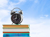 Books and an alarm clock on a background of blue sky  — Stockfoto