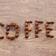 Word coffee written with coffee beans on wooden background — Stock Photo #51272951