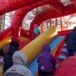 Children ride on inflatable slides — Stock Video #13217607
