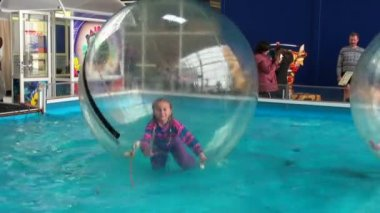 Children in spheres on water — Stock Video