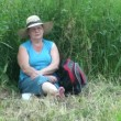 Elderly woman sitting in the grass — Stock Video