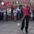 Man juggling soccer ball on a street in front of crowd — Stock Video