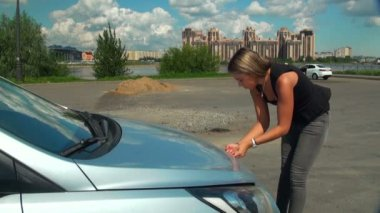 Blonde opens the hood of a car — Stock Video