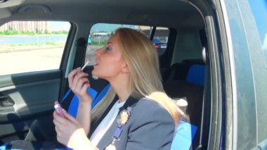 Blonde in the car paints her lips — Stock Video