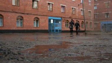 Gevangenen in de tuin van het gebouw onder een regen — Stockvideo
