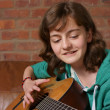 Teenage girl playing the guitar — Stockfoto