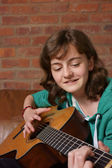 Teenage girl playing the guitar — Stock Photo