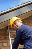 Builder or roofer climbing a ladder — Stock Photo