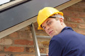 Builder or roofer on a ladder — Stock Photo