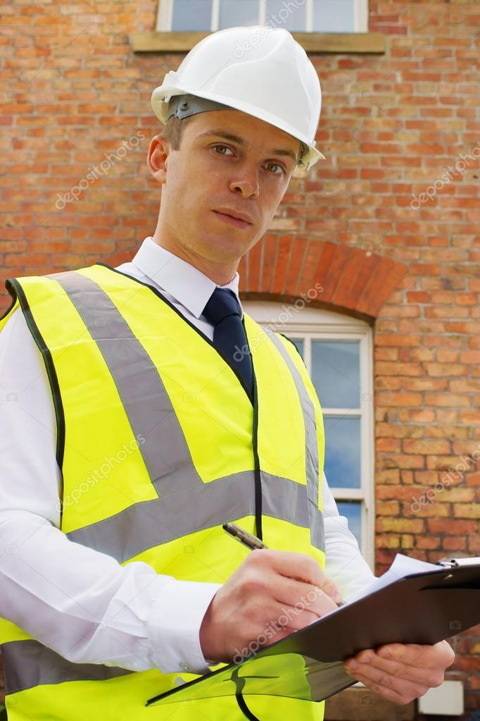 A construction professional outside a brick building, an inspector, surveyor or project manager. — Stock Photo #12417932