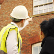 Surveyor or builder and homeowner looking at a property - Stock Photo