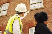 Geometra o generatore e proprietario di abitazione guardando una proprietà — Foto Stock