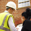 Surveyor or builder and homeowner discussing property issues - Stock Photo