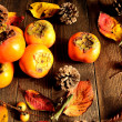 Persimmon,fall leaves and pine cone — Stock Photo