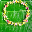 Lei of Asian tropical flowers on banana leaf background - Stock Photo