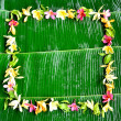 Asian tropical flowers on banana leaf background - Stock Photo