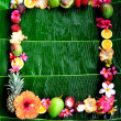 Tropical fruits and flowers on banana leaf background. — Stock Photo