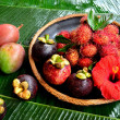 Asian tropical fruits with red hibiscus — Stock Photo #22484201