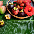 Asian tropical fruits with red hibiscus — Stock Photo #22484223